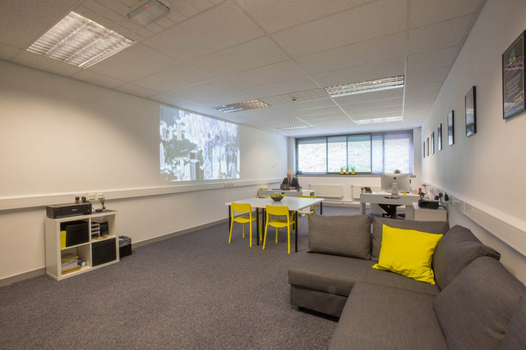 Barnsley office space at The Business Village, Wilthorpe, grey sofa with yellow cushion, white table with yellow chairs, projector pointed at wall