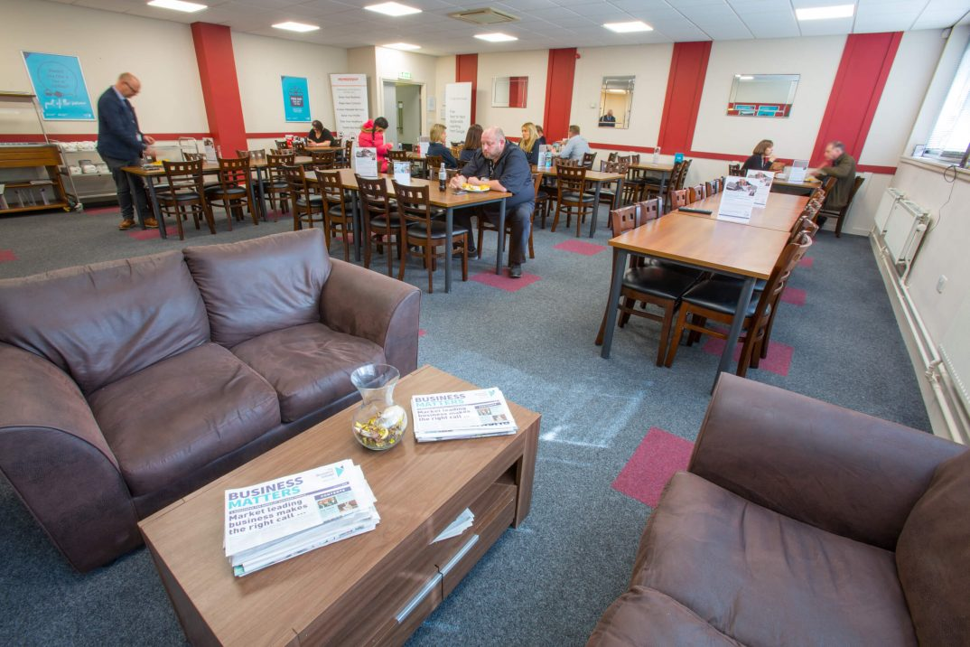 Barnsley office space cafe, brown leather sofas, tables & chairs, people eating and drinking