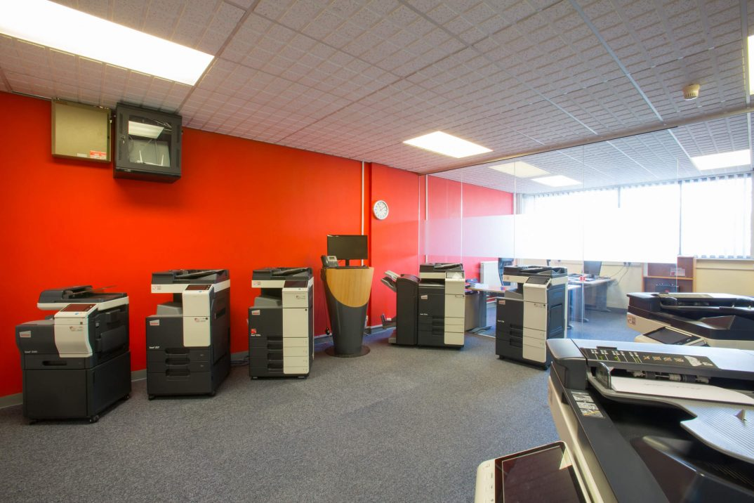 Branded Barnsley office space full of large printers and scanners with a glass walled off section with a desk