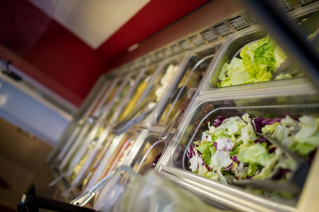 Catering tubs filled with a variety of meal and salad components